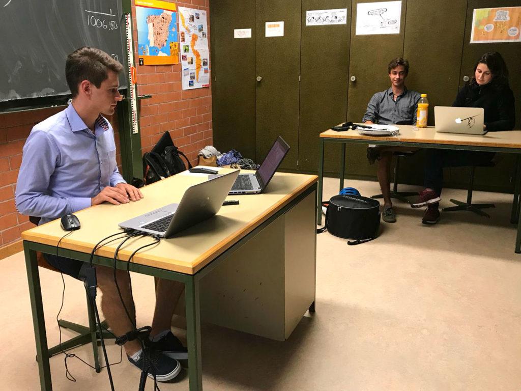 Man sitzt an einem Schreibtisch mit zwei Laptops