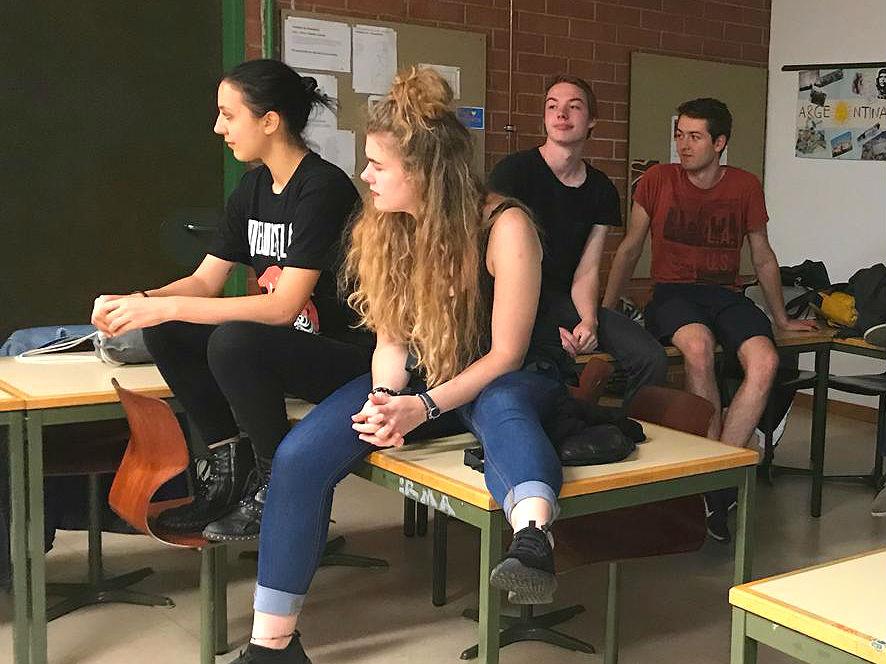 Vier Menschen auf Tischen sitzend.